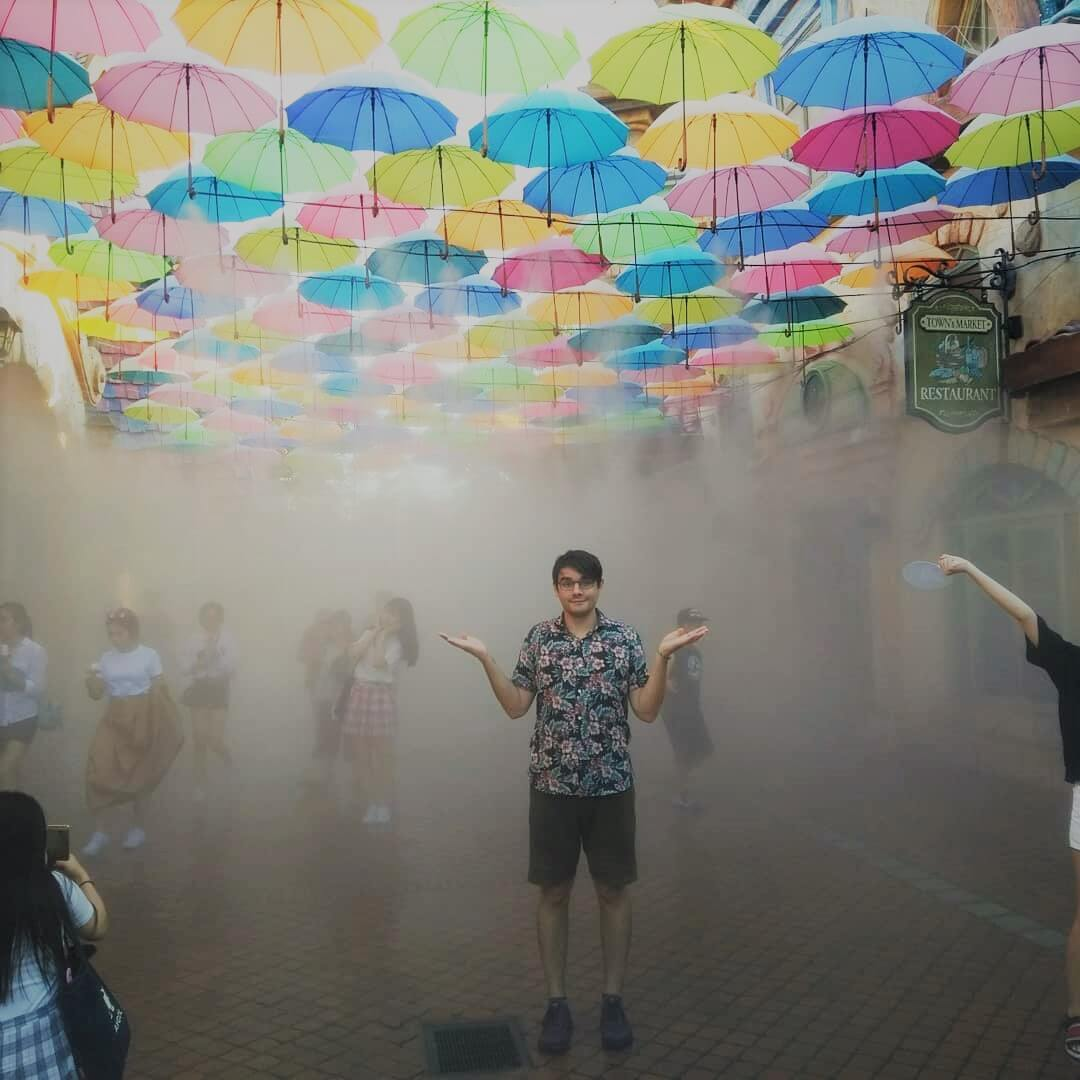 A picture of Tom Burton standing under many colorful umbrellas in the mist